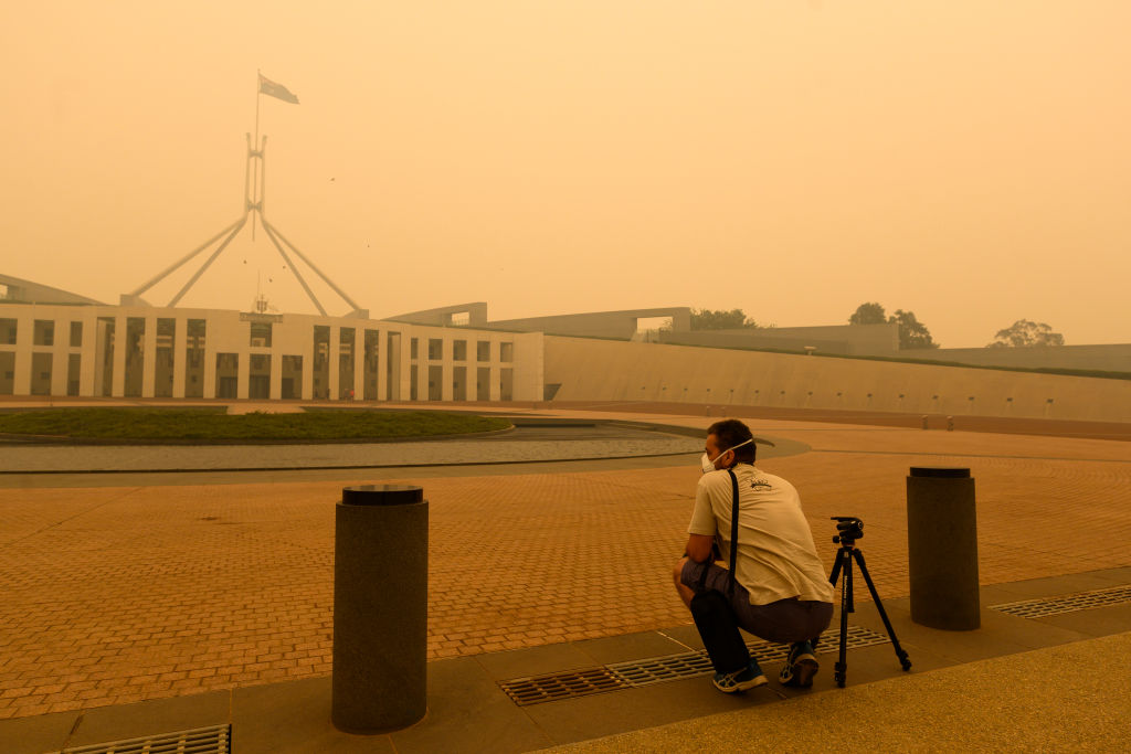 CANBERRA, AUSTRALIA - JANUARY 05: A photographer captures smoke at Parliament House on January 05, 2020 in Canberra, Australia. Smoke haze across Eastern Australian cities has become common in recent months as bushfires continue to burn. Hundreds of fires continue to burn in NSW, Victoria and South Australia, with the Australian Defence Force now called in to help with firefighting and rescue efforts. 14 people have died in the fires in NSW, Victoria and SA since New Year's Eve. (Photo by Rohan Thomson/Getty Images
