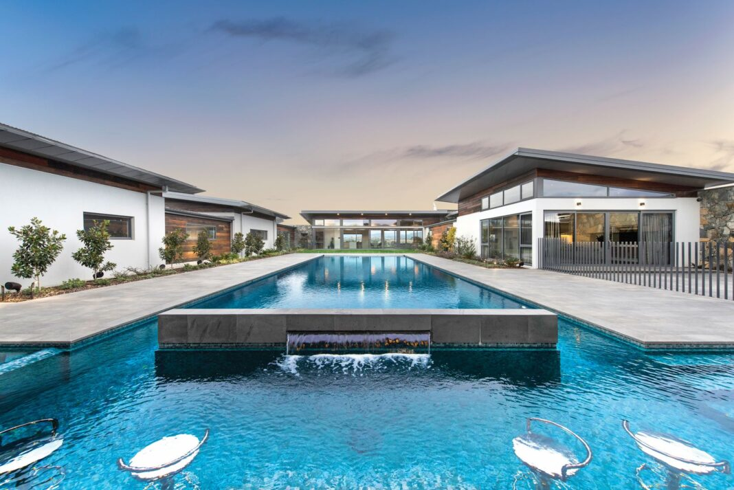 large pool with water feature on backyard of large home