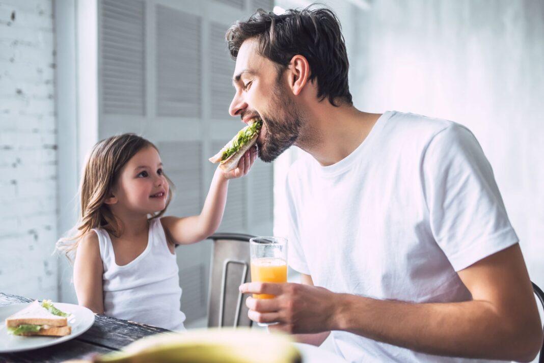 little girl feeding her dad a sandwich