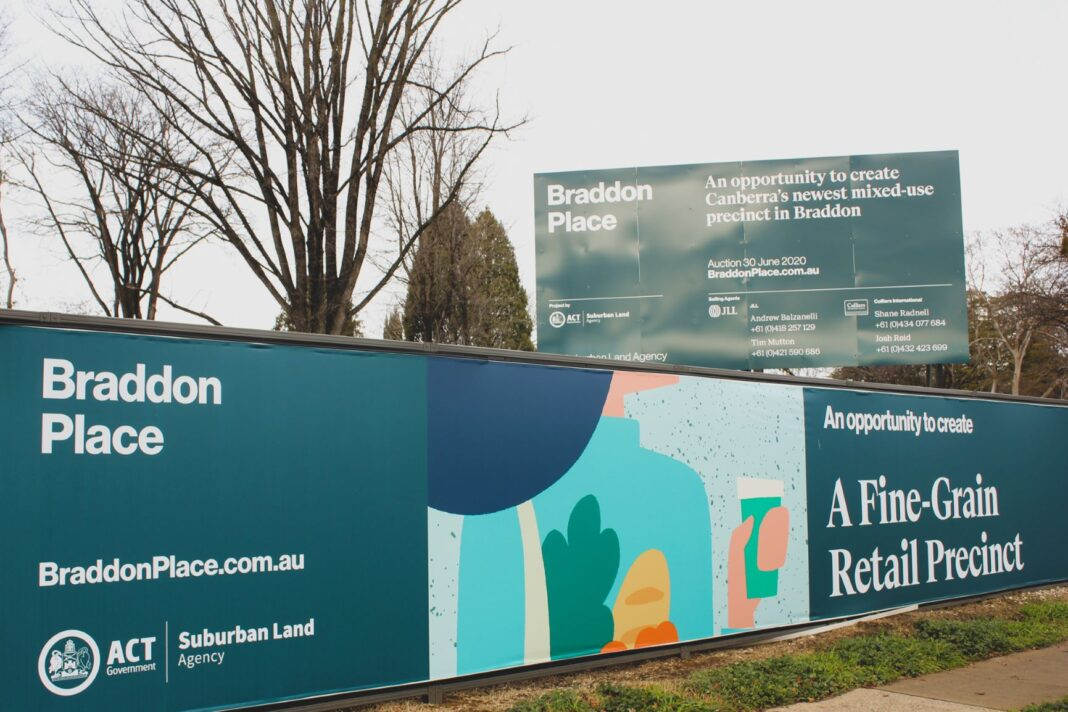 brightly coloured hoardings around a vacant block of land on Northbourne Avenue, Canberra that has just been sold to a developer