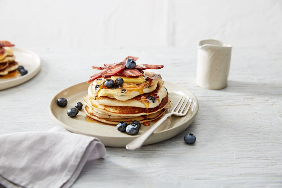 Stack of pancakes topped with blueberries, maple syrup and bacon strips on a white plate.