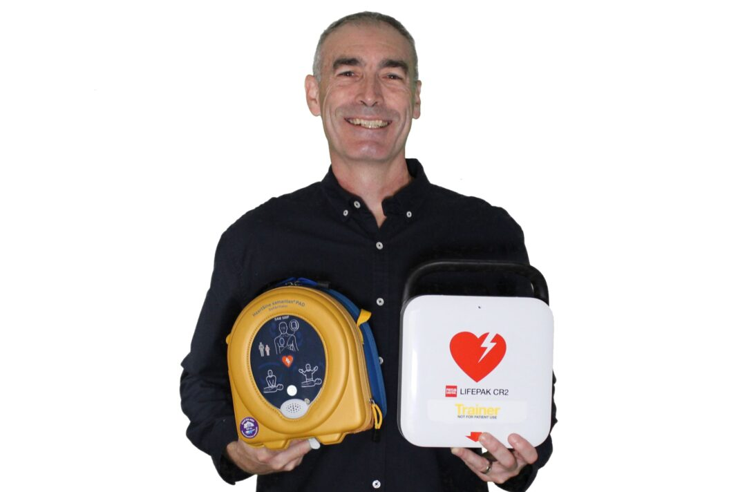 Smiling middle aged man holding a yellow defibrillator and a heart health first aid kit