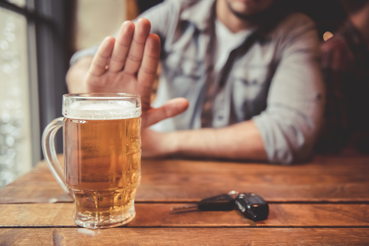 Cropped image of man showing stop gesture and refusing to drink beer. Car keys lying near.