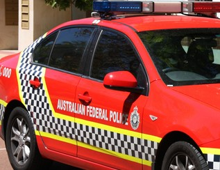 Side-on view of part of a red Australian Federal Police sedan with lights on top