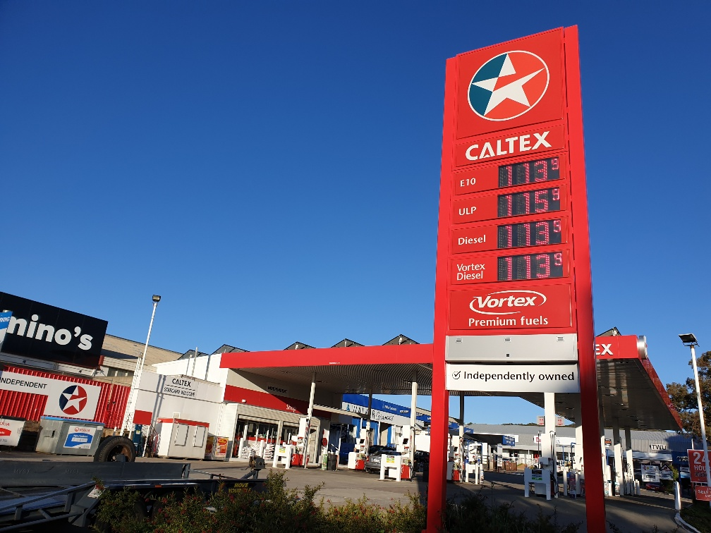 Caltex petrol station with big red sign displaying fuel prices set against a bright blue sky
