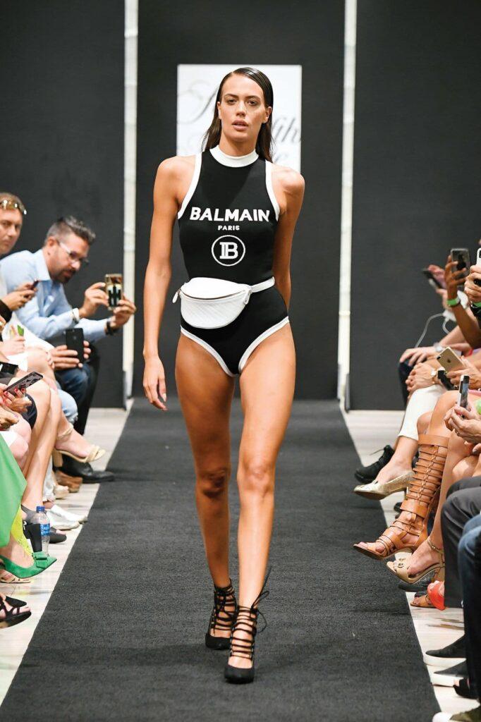 woman walking on a catwalk in a bathing suit