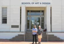 A man and woman standing outside the School of Arts & Design, an art deco building at the Australian National University