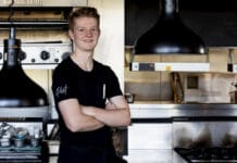 Teenage boy in t-shirt standing in commercial kitchen