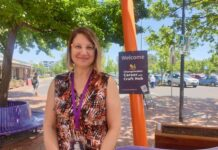 Smiling woman standing near Changemaker Career and Craft Hub sign outside in dappled sunlight