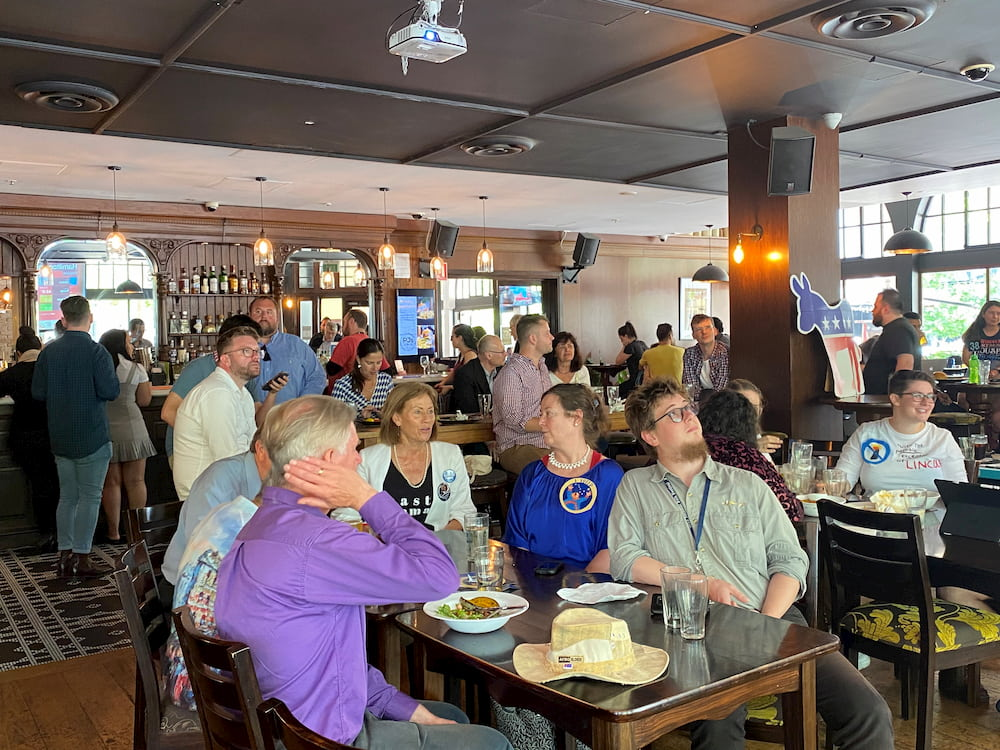 A group of Canberra residents with strong ties to the United States sit watching the presidential race in a pub.