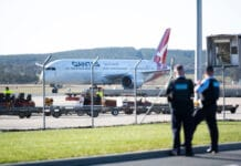 Police watch a repatriation flight from Delhi arrive at Canberra Airport in May. (Photo by Rohan Thomson/Getty Images)