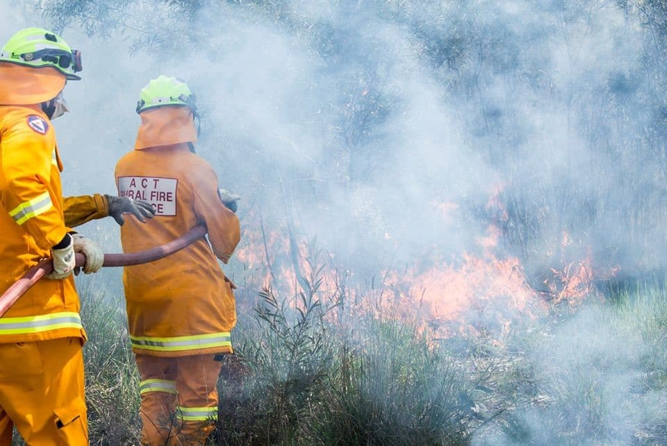 Two ACTRFS volunteers battle flames during last year's bushfire season