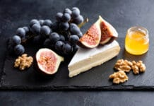 a cheese board with brie, figs, grapes and honey