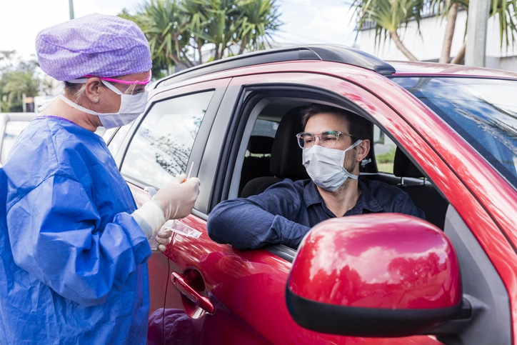 A female doctor in a protective suit taking a nasal swab from a man in a red car for possible coronavirus infection
