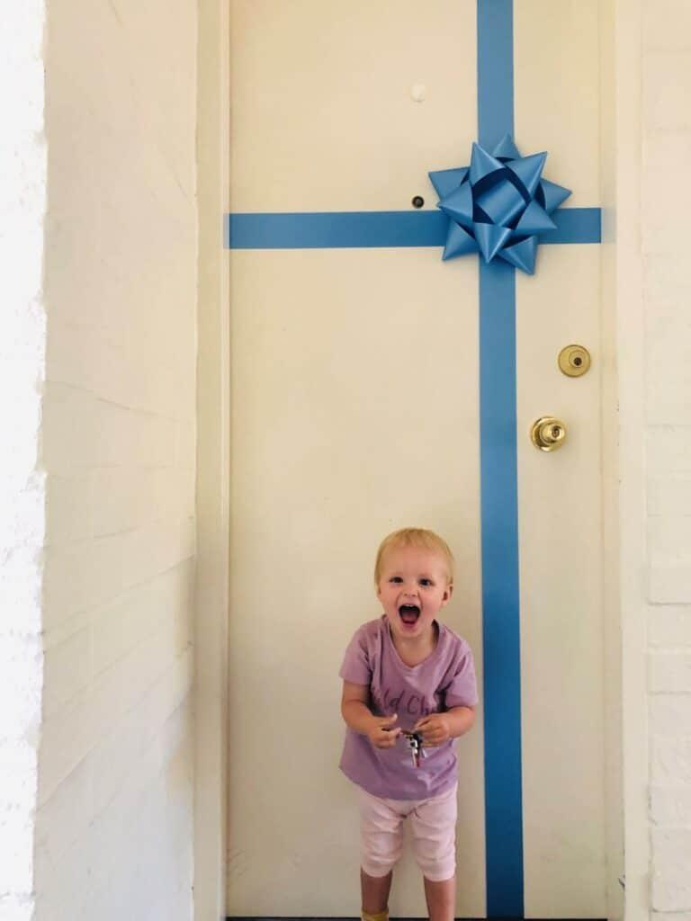 little girl smiling in front of a door
