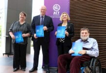 Two women, one man standing and one man in wheelchair holding Disability Action and Inclusion Plan documents