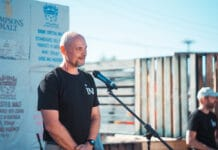 middle aged bald man in black t-shirt speaking into microphone on an outdoor stage
