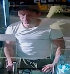 CCTV image of man in white t-shirt at shop counter paying by card