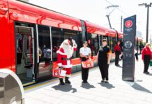 Santa and helpers standing on a tram platform near a red light rail vehicle