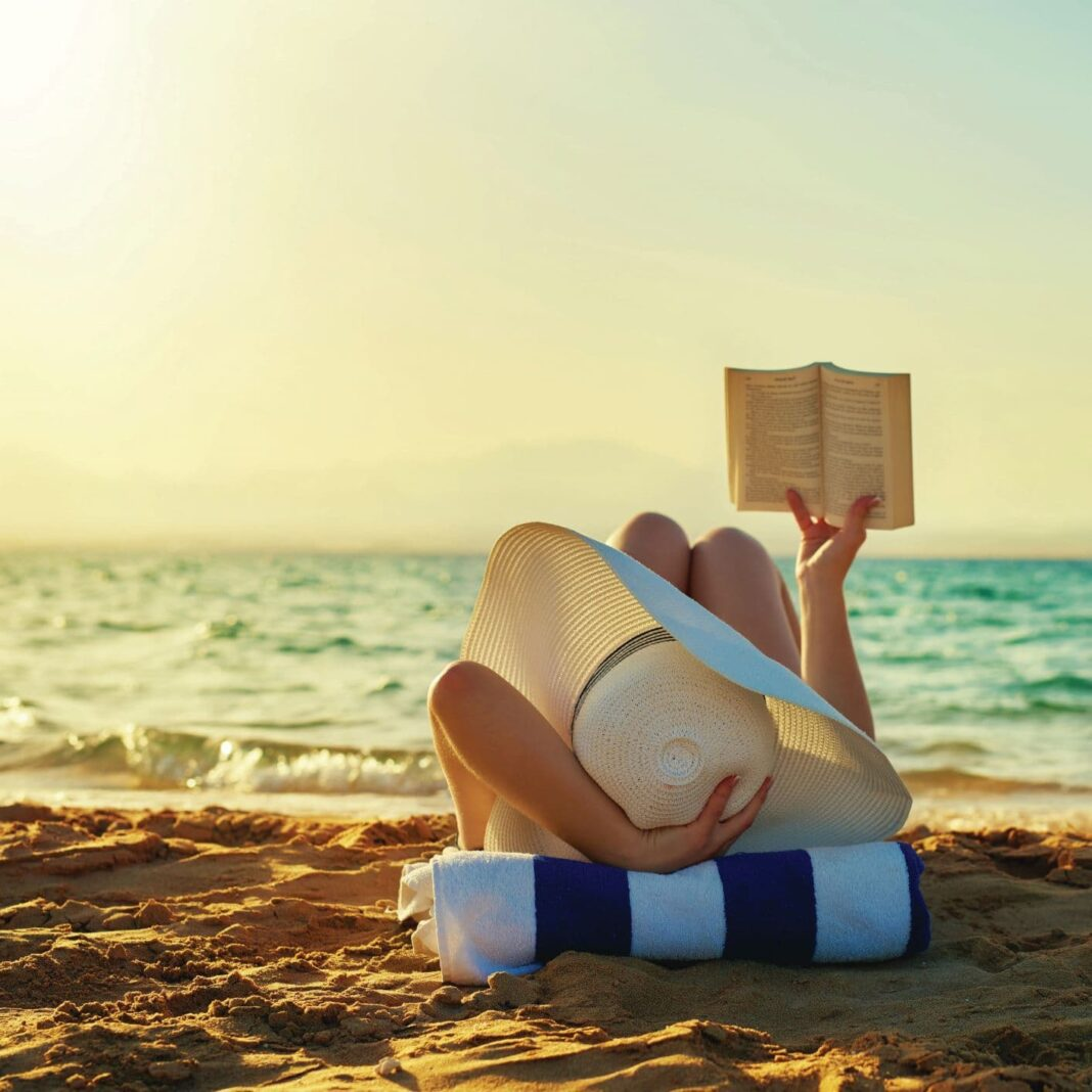 woman reading a book by the beach