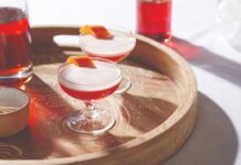 two red cocktails in glasses on a wooden tray