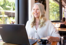 The 5:30am Club Canberra founder Emily Davidson sits at a café table smiling, with her laptop open