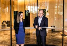 middle aged man cutting ribbon in a shiny new hotel foyer as woman in blue dress looks on