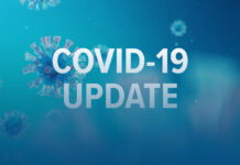 covid-19 update signage on blue background with graphics of coronavirus in blue