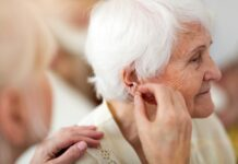Female doctor applying hearing aid to senior woman's ear