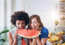 two women biting into a watermelon