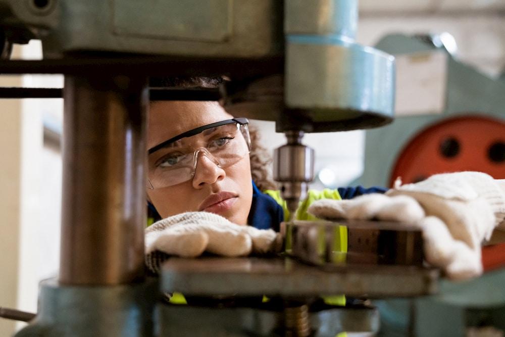 Female apprentice using yoke machine in factory