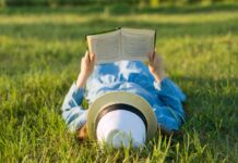 person laying on the grass reading