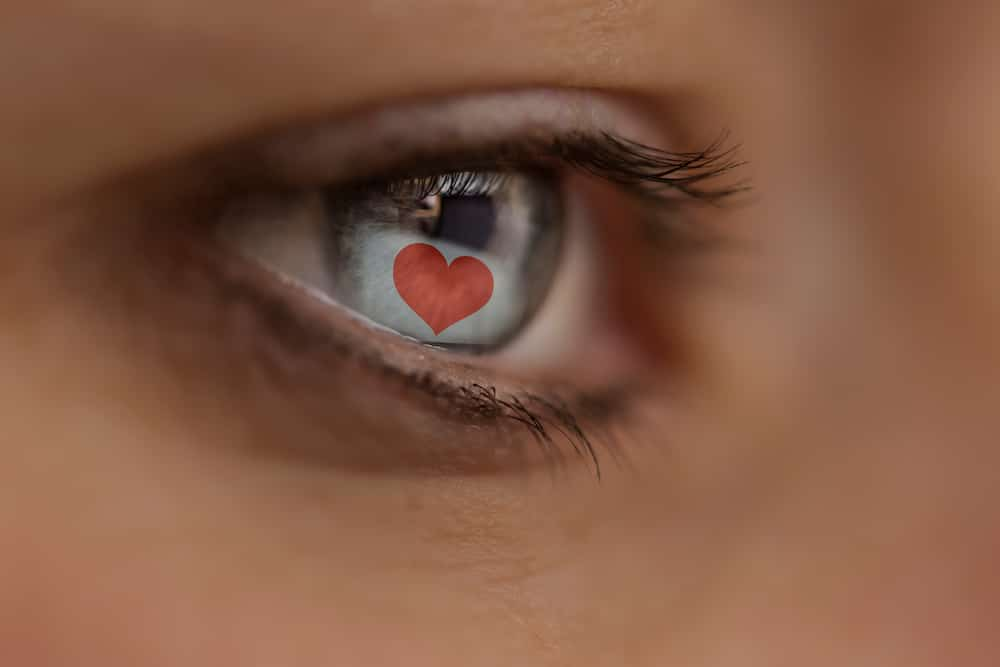 A photo of an eye showing the reflection of a love heart on a computer screen to symbolise online dating