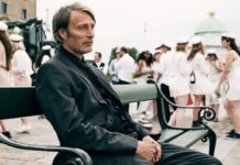Mads Mikkelsen sitting on a bench