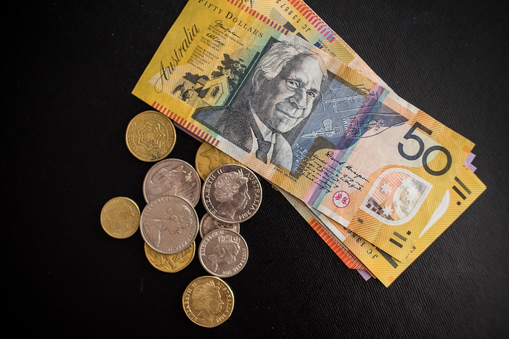 Australian coins and a fifty dollar note lie on a black background, to symbolise the pocket money kids will no longer be able to bank with Dollarmites in ACT.