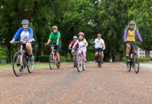 Six people in bikes, of all ages and abilities, ride toward the camera with smiles in their faces - they will all participate in the Big Canberra Bike Ride