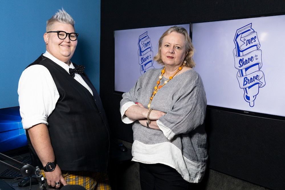 Sue Webeck wears a black vest and white collared shirt, her hair is an icy blonde colour and she wears glasses. Glenda stands to her right with her arms crossed and a light grey long sleeve shirt, she has shoulder length blonde hair. Both women are participating in Shave for the Brave.