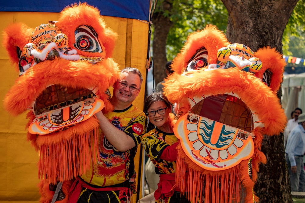 A man and a woman from a lion dance troupe hold their costumes and smile, celebrating Lunar New Year in Canberra.