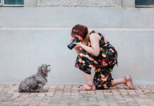 Ina Jalil of Ina J Photography, kneels and takes photo of a small grey dog.