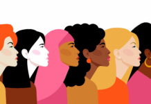 An illustration of women of different ethnic backgrounds stand in a row facing the same direction, for International Women's Day.