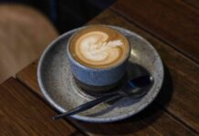 latte art on a coffee in a speckled stoneware cup on a stoneware saucer with teaspoon alongside