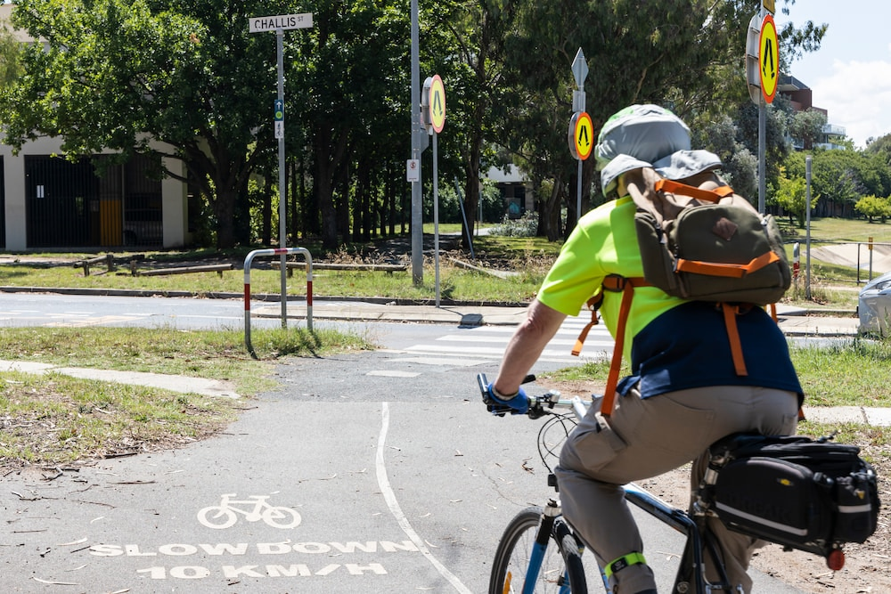 A man with a green tshirt rides towards a pedestrian crossing in Dickson, one of the most frequent sites for bicycle crashes in the act.
