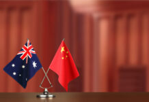 Two crossed national flags of Australia and China on wooden table