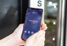 An iPhone XS displays the Check In CBR app in front of a glass door