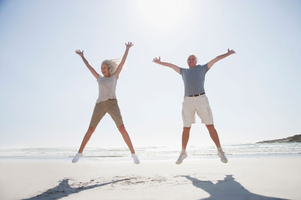 two elderly people jumping for joy on the beach