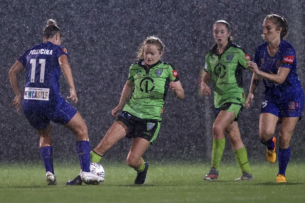 four professional female soccer players, two in green and two in blue, playing football in pouring rain