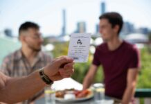 male hand holding a lottery ticket with two other men and city skyline blurred in the background