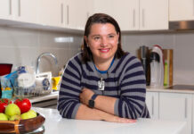 YWCA Rentwell landlord Serina Bird leans on her white kitchen bench with a fruit bowl in the foreground, smiling and looking off camera, wearing a grey and black striped jumper. She has short brown hair and white skin.