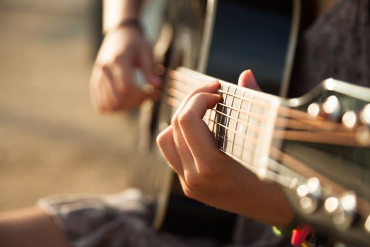 Teen girl playing acoustic guitar, detail, shallow DOF.
