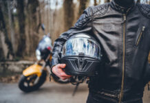 A motorcyclist stands in front of the camera, pictured from below the chin to the waist, holding a helmet against his hip. Today ACT Policing said motorcyclist deaths were overrepresented in ACT.